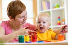 Pittura del bambino e della madre insieme a casa Fotografia Stock Libera da Diritti