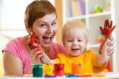 Pittura del bambino e della madre insieme a casa Immagini Stock Libere da Diritti
