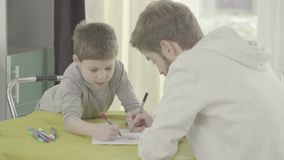 Pittura del figlio e del padre su carta che si siede nel salone alla tavola relazione del Padre-bambino archivi video