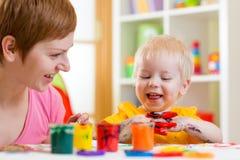 Pittura del ragazzo del bambino e della mamma insieme a casa Fotografie Stock
