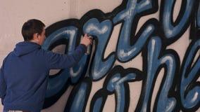 Pittura dell'artista dei graffiti con lo spruzzo di aerosol sulla parete Fotografie Stock