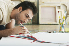 Pittura dell'uomo sulla tela sul pavimento dello studio Fotografie Stock Libere da Diritti