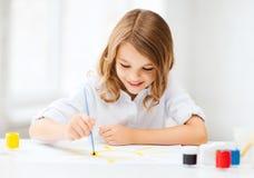 Pittura della bambina alla scuola Fotografia Stock
