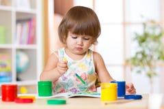 Pittura della bambina nella scuola o nel centro daycary Istruzione immagini stock libere da diritti