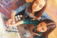 Pittura della ragazza e dell'insegnante femminile sulla tela da dipinto insieme Immagini Stock