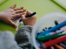 Pittura di tre anni della ragazza con i colori sulla tavola verde fotografia stock