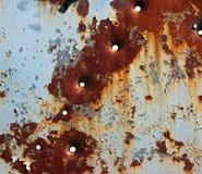 Pittura e fori di pallottola di sfaldamento su di piastra metallica arrugginito Fotografia Stock