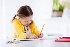 Pittura e scrittura della bambina Fotografia Stock