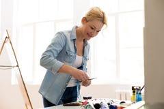 Pittura felice dell'artista della donna allo studio di arte Fotografie Stock