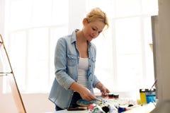 Pittura felice dell'artista della donna allo studio di arte Immagine Stock Libera da Diritti