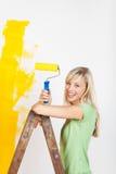 Pittura felice della donna sulla scala Immagini Stock