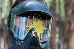 Pittura gialla della macchia su una maschera del vetro di protezione per il gioco del paintball fuori La testa di un giovane in u immagini stock libere da diritti