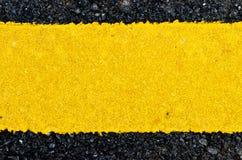 Pittura gialla ruvida del primo piano sulla strada asfaltata Fotografia Stock