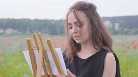 Pittura graziosa della giovane signora su una piccola condizione del cavalletto sul campo del papavero L'artista femminile all'ap archivi video