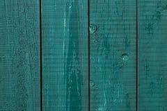 Pittura incrinata del recinto di legno I bordi di legno approssimativi hanno dipinto verde Fondo di legno di struttura, recinto d fotografia stock libera da diritti
