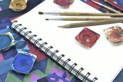 Pittura, matita e pennello usati di colore di acqua sul libro bianco Immagine Stock