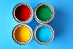 Pittura multicolore in barattoli di latta sul fondo di colore Fotografia Stock