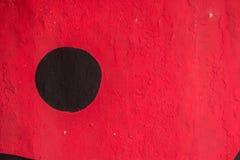 Pittura nera del cerchio in una parete rossa Fotografia Stock Libera da Diritti