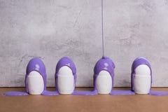 Pittura porpora che versa sulle uova in tazze Fotografia Stock Libera da Diritti