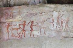 Pittura preistorica dal cavernicolo locale primitivo sulla parete di pietra che mostra la caccia e la civilizzazione in 4000 anni immagini stock libere da diritti
