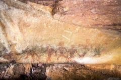 Pittura preistorica degli uomini nelle azioni su roccia dipinta con colore rosso dall'essere umano che vivono nell'area in mille  immagine stock