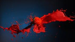 Pittura rossa che spruzza con la palla sul blu fotografia stock