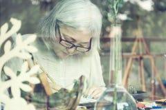Pittura senior asiatica della donna al suo studio domestico Immagine Stock Libera da Diritti