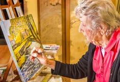 Pittura senior della donna al suo cavalletto, nel suo studio in Francia Fotografia Stock