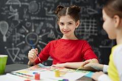 Pittura sorridente della scolara in Art Class Fotografia Stock