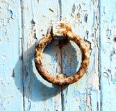 pittura spogliata sporca del chiodo arrugginito del metallo nella porta di legno blu e Fotografia Stock