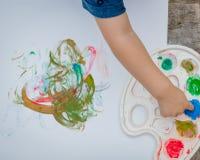 Pittura sveglia del ragazzino con le mani di una pittura facendo uso delle pitture impacciate Fotografia Stock Libera da Diritti