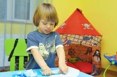 Pittura sveglia del ragazzo con le sue dita immagine stock libera da diritti