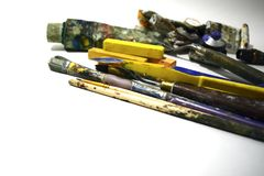 Pitture ad olio multicolori e vecchie spazzole su un fondo bianco fotografia stock