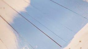 Pitture del pittore sopra un bordo di legno con pittura blu stock footage