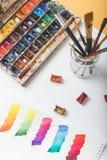 Pitture dell'acquerello, pennelli e colpi variopinti della pittura nell'album del disegno nel luogo di lavoro del progettista Immagine Stock