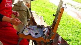 Pitture dell'artista di paesaggio in oli misti sulla spazzola di pittura dei circuiti di uscita della tavolozza stock footage