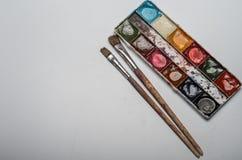 Pitture multicolori e spazzole dell'acquerello per la bugia di disegno su un foglio bianco di carta su un fondo bianco Fotografia Stock Libera da Diritti