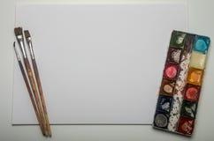 Pitture multicolori e spazzole dell'acquerello per la bugia di disegno su un foglio bianco di carta su un fondo bianco Fotografia Stock