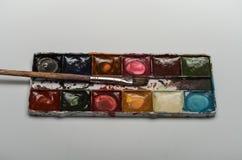 Pitture multicolori e spazzole dell'acquerello per la bugia di disegno su un foglio bianco di carta su un fondo bianco Immagini Stock