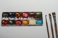 Pitture multicolori e spazzole dell'acquerello per la bugia di disegno su un foglio bianco di carta su un fondo bianco Immagine Stock Libera da Diritti