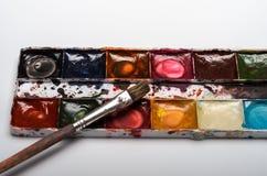 Pitture multicolori e spazzole dell'acquerello per la bugia di disegno su un foglio bianco di carta su un fondo bianco Immagine Stock