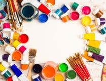 Pitture, spazzole e tavolozza sui precedenti di legno bianchi immagini stock
