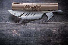 Piuma bianca del rotolo di carta antico sul bordo di legno Fotografia Stock