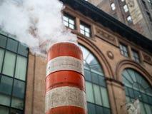 Piuma dell'aumento del vapore dalla via della città attraverso bianco e la o giganti fotografia stock libera da diritti