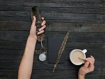 Piuma e tazza di caffè in una mano ed in un taccuino femminili Vecchio corteggi Immagini Stock