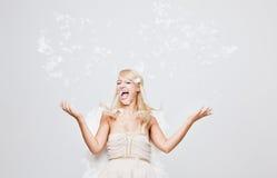 Piume di lancio di angelo biondo felice Immagine Stock