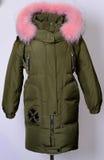 Piumino di inverno con il collare rosa della volpe su un fondo grigio outerwear Fotografia Stock