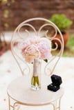 Pivoines douces de bouquet de mariage avec des anneaux Images stock