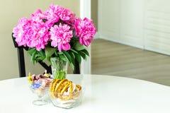 Pivoines en vase en verre, bonbons et bagels sur une table ronde blanche Image stock