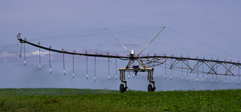 Pivot irrigation system in operation watering Royalty Free Stock Photos